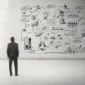 man looking at business strategy on a wall